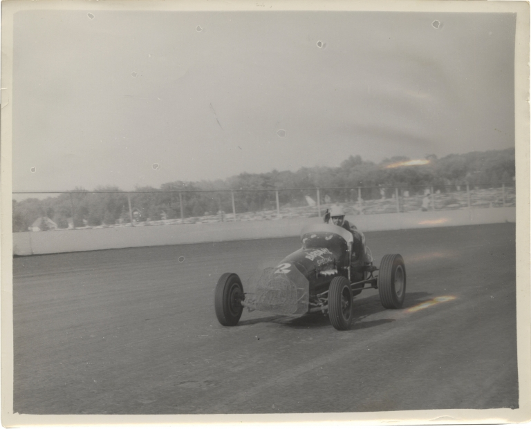 Archive of 14 vernacular photographs of open wheel races at the Iowa State Fair, circa 1950s. Auto Racing.