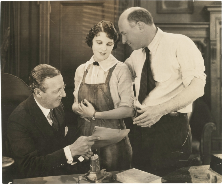 """Original press photograph of Leatrice Joy being presented a """"star contract"""" by Cecil B. DeMille and Jesse L. Lasky, 1924. Cecil B. DeMille, Leatrice Joy, Jesse L. Lasky, subjects."""
